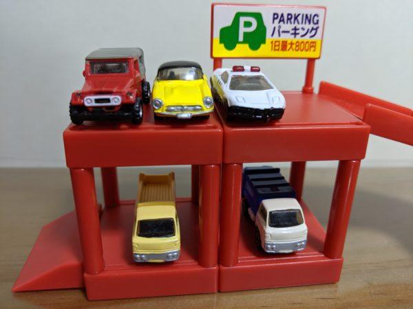 色んなミニカーが赤い台の上に並んでる写真