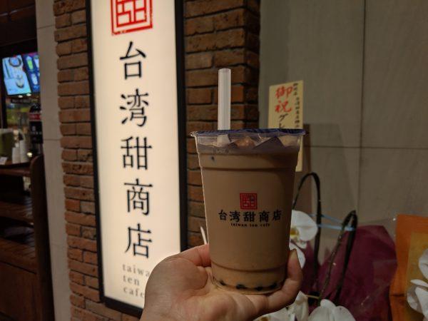 お店の看板と甜ミルクティーの写真